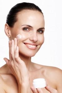 Pretty woman smiling while applying skin cream toher cheek